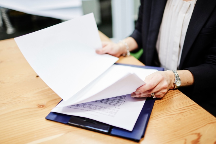 Woman looking over papers attached to a clipboard.