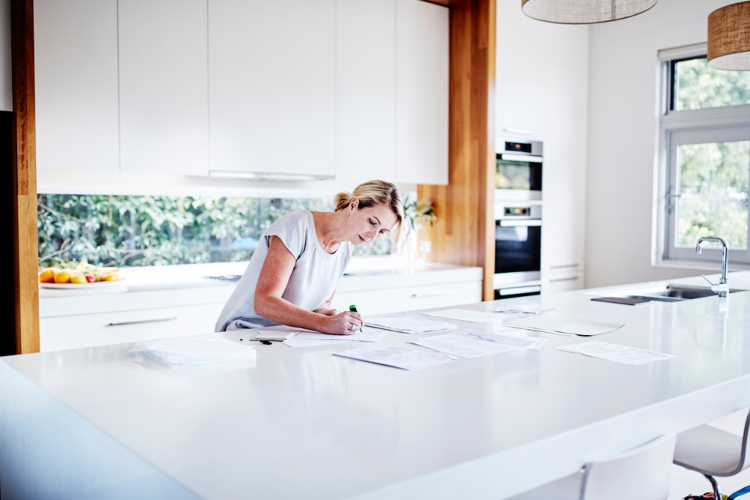 Woman highlights papers on a white benchtop.